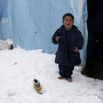 A Syrian refugee boy reacts as he stands barefoot on snow outside a tent at a refugee camp in Zahle